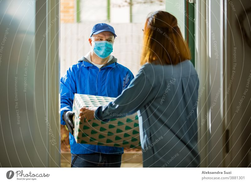 Delivery man bringing holiday packages. Woman at home standing in doorway, receiving parcels for Christmas gifts. Delivery guy in protective mask and gloves.