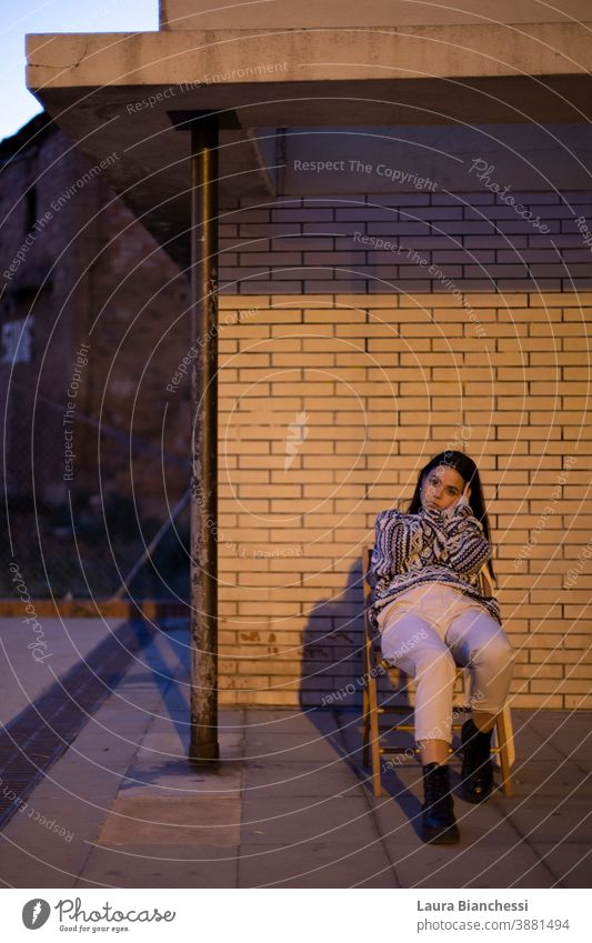 Portrait of young woman sitting on a chair in a porch in front of a brick wall wearing a winter sweater and white pants Young woman girl blue blue light black