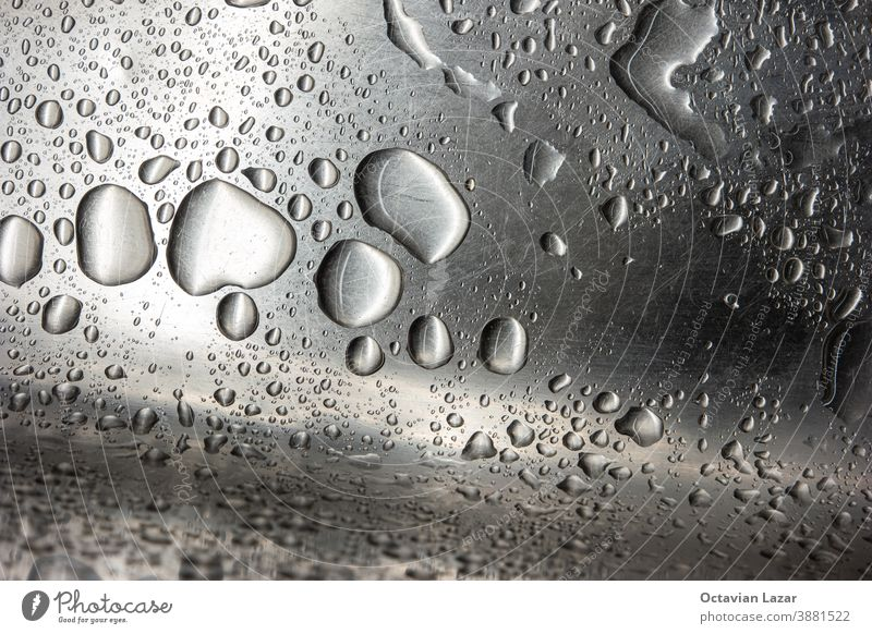 Stainless metal kitchen sink macro close up shot with big water droplets and scratched surface texture close-up circular splash background tap swirl waste shiny