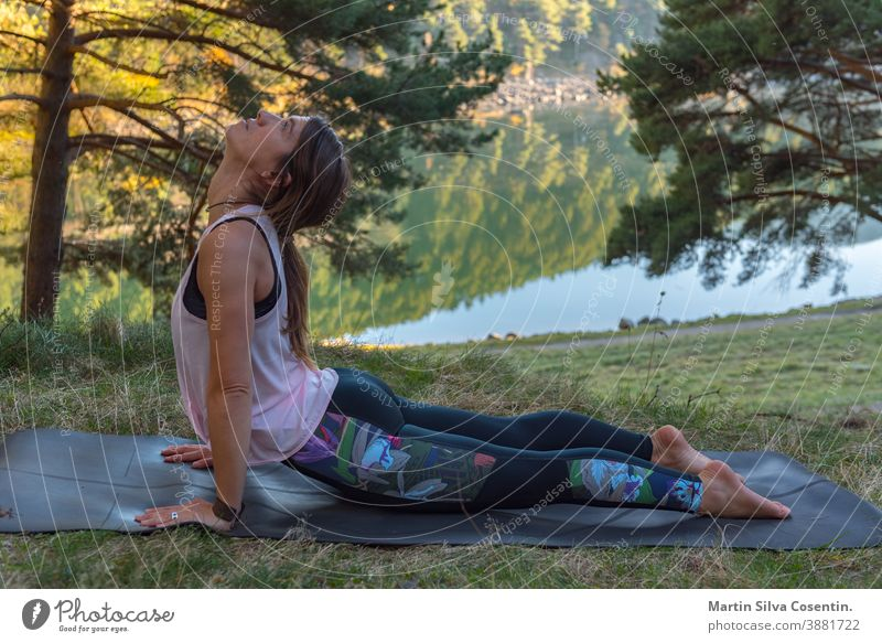 Woman practices yoga alone in the forest Back view Outdoor activity Young attractive woman practicing yoga, exercising exercising working out Women is meditating alone at sunrise.
