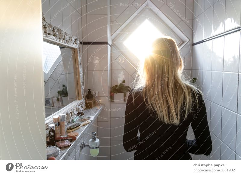 Rear view of a blonde woman standing in a bathroom Woman Blonde Back-light Bathroom Sunlight care hygiene indoors Tile Colour photo Interior shot Mirror White