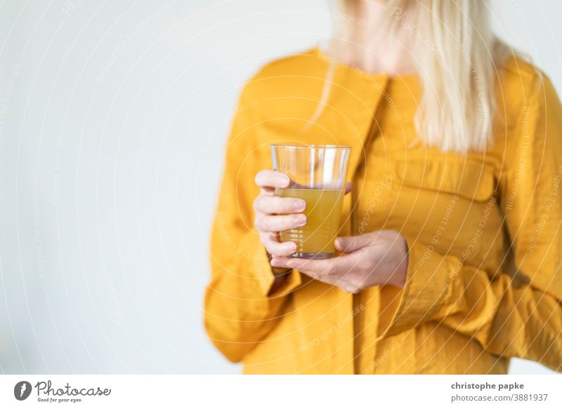Blonde woman holding glass with lemonade Woman Orange juice Lemonade Glass Drinking drinking glass stop Beverage Juice Cold drink Fresh Delicious Refreshment