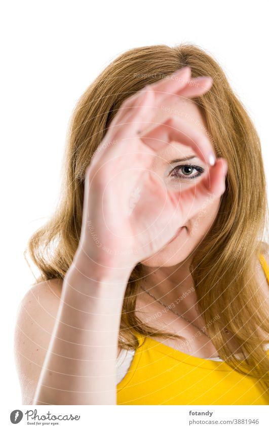 Looking through the ok sign Frau jung kaukasisch Blick in die Kamera weißer Hintergrund isoliert Auge Augenblick Handzeichen O.K.-Zeichen Fokus Gesicht verdeckt
