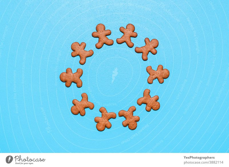 Gingerbread man cookies arranged in a circle on a blue background. above view biscuits celebration christmas copy space cut out decoration dessert festivity