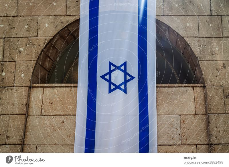 Israel flag, flag with Star of David hung on a building Flag Blue Part of a building Building National Holocaust memorial Religion and faith White Sign Landmark