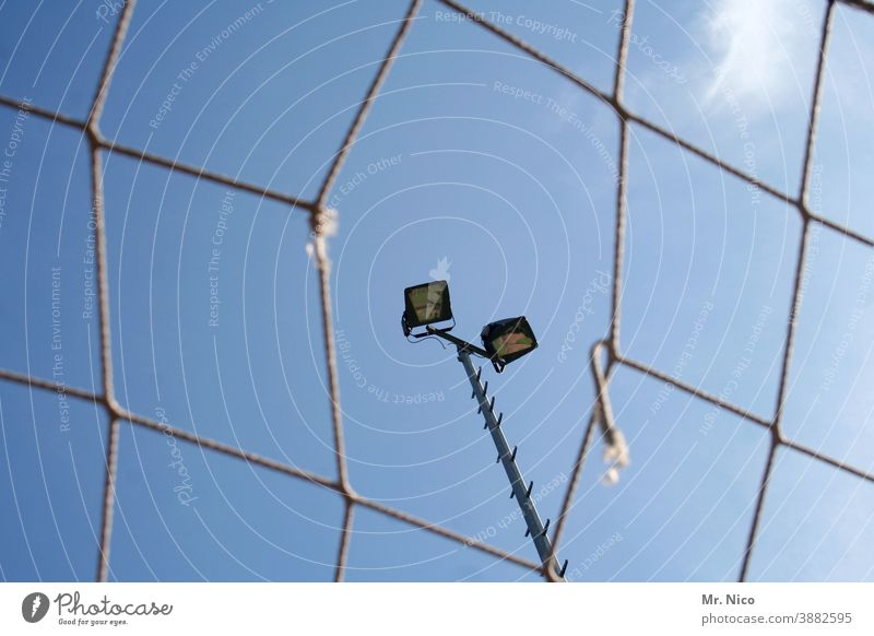 A hole in the net Net Floodlight Stadium Sporting Complex Leisure and hobbies Football pitch Light Lighting Hollow Sky Blue sky Ball sports Sporting event Pole