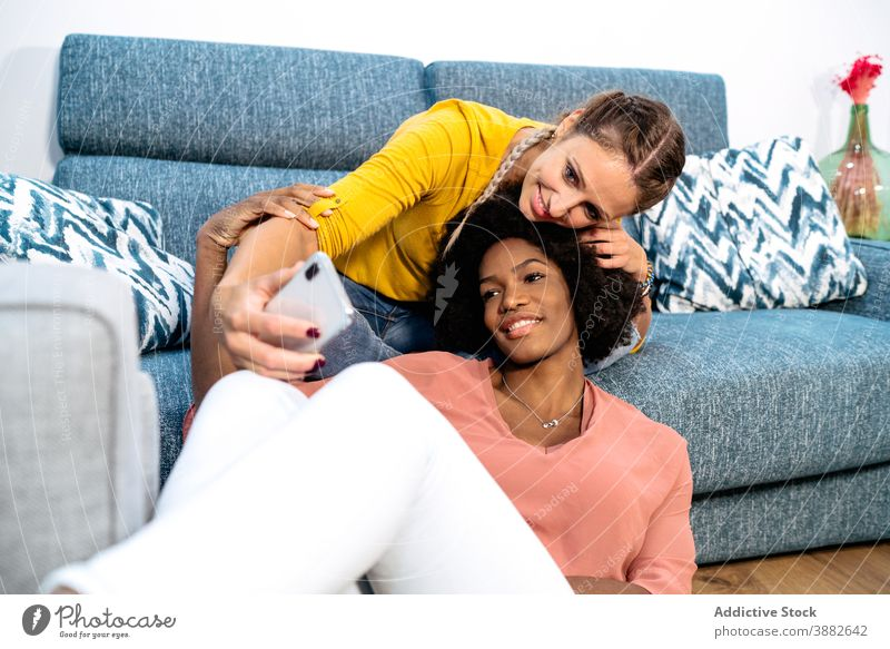 Happy diverse girlfriends taking selfie at home women couple cuddle relax lesbian together relationship smartphone take photo mobile shoot sofa female love