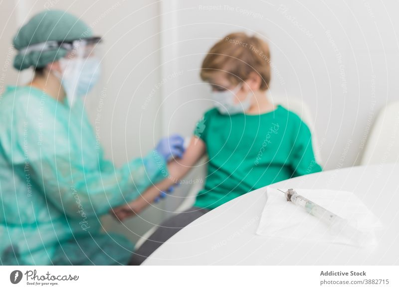 Doctor preparing child for vaccination from coronavirus disinfect injection patient vaccine doctor sterile covid 19 new normal costume medic clinic protect