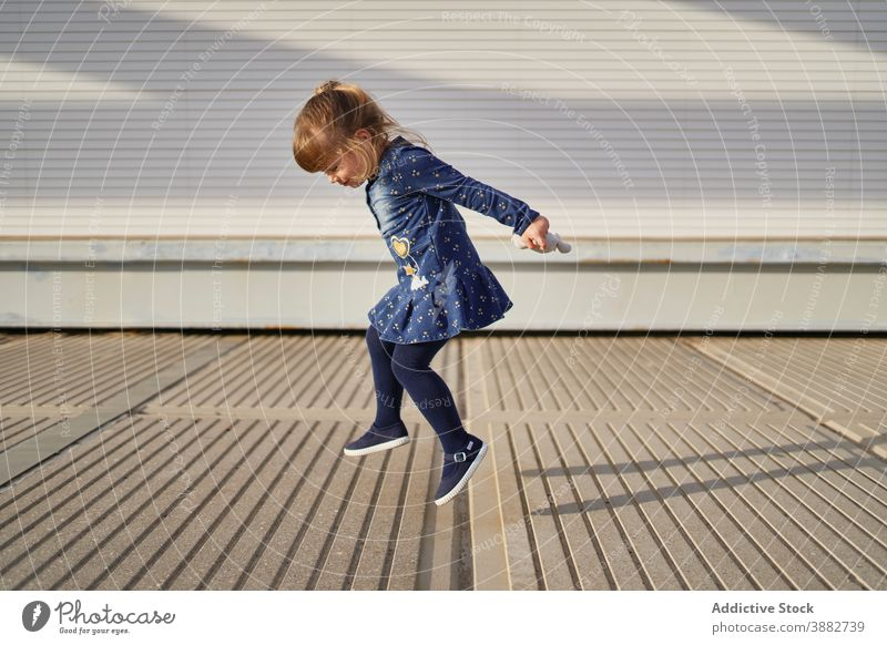 Happy girl jumping on street child leap carefree having fun play funny playful cheerful entertain game weekend city above ground little kid joy content happy