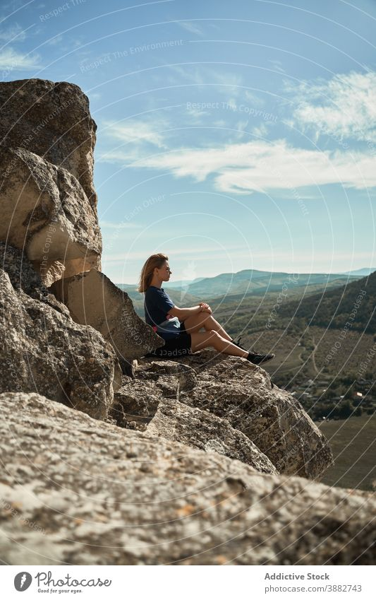 Traveling woman sitting on rock in highlands hiker mountain trekking viewpoint relax freedom enjoy hill female rocky adventure majestic scenery tourism summer