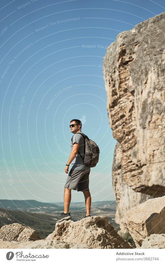 Man with backpack on rock in mountains traveler hiker man vacation summer wanderlust adventure highland male explorer spectacular picturesque landscape journey