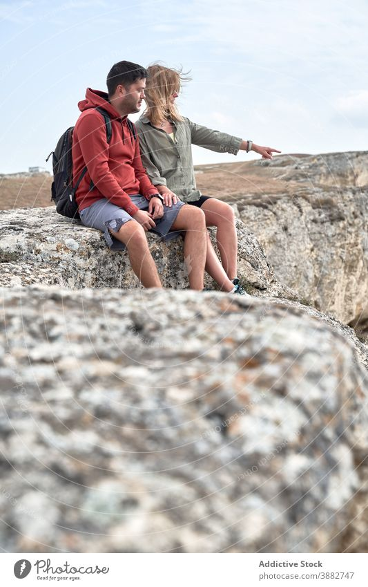 Traveling couple resting on hill during trekking travel hiker rocky mountain relax explorer together nature landscape tourism vacation relationship highland
