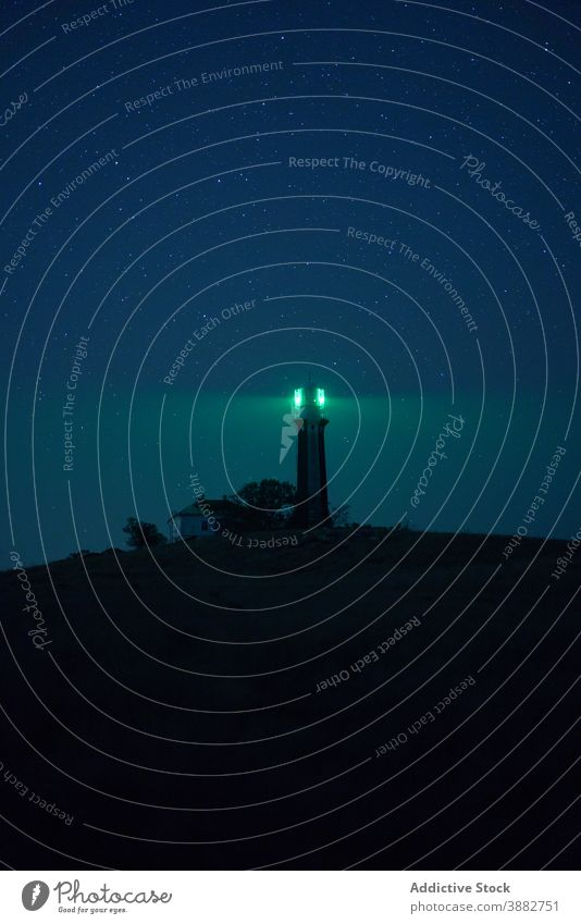 Lighthouse glowing at night against starry sky lighthouse beacon hill tower illuminate green landscape nature picturesque twilight architecture spectacular
