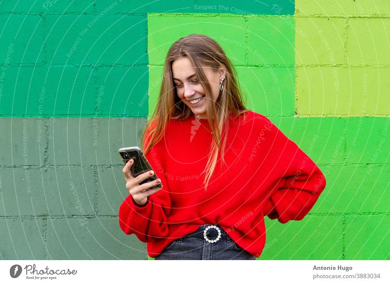 Teenage blonde girl with a red sweater surfing with her mobile phone. Green wall background smiling teenager green background smile positive chic laugh naughty