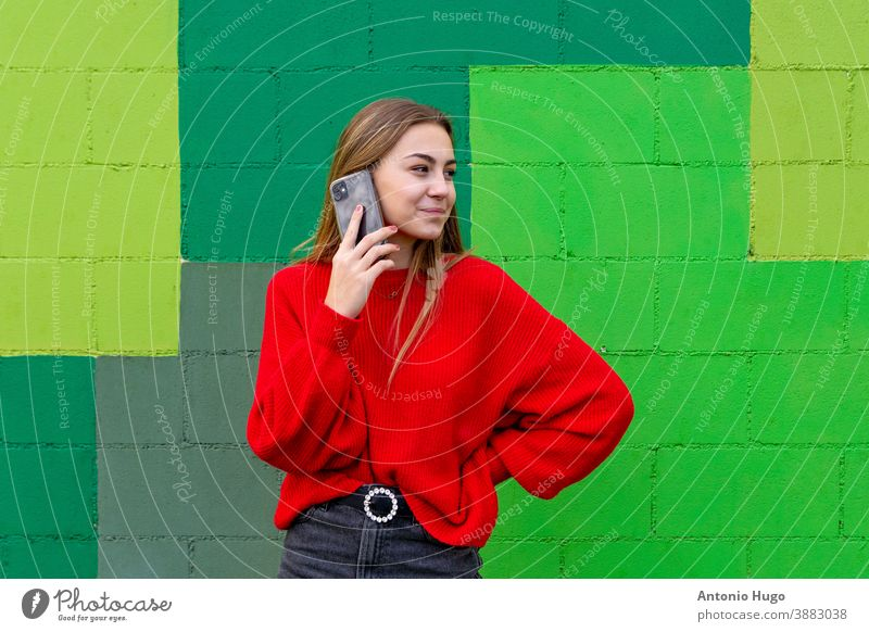 Teenage blonde girl with a red sweater speaking with her mobile phone. Green wall background smiling teen green background teenager smile positive chic laugh