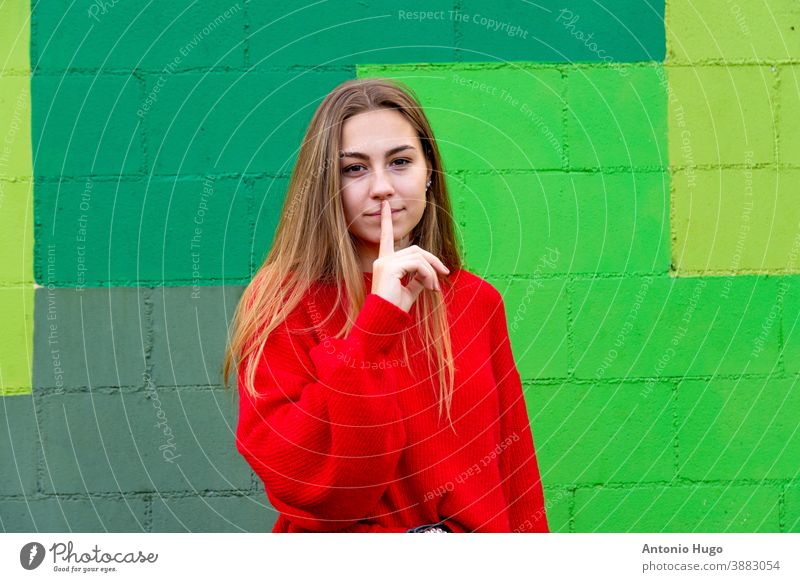 Teenage blonde girl with a red sweater. Shuts up. Green wall background positivism green background teenager smiling positive smile chic laugh naughty happiness