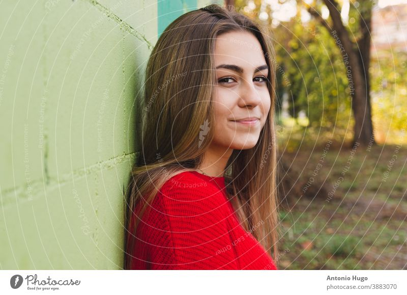 Teenage blonde girl with a red sweater. Smiling . Green wall background thoughtful thinking posing leaning camera smiling teen positivism green background