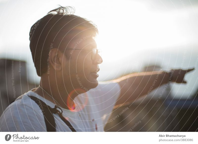 Close up portrait of a middle aged Indian Bengali bulky guy with spectacles in a casual mood on the rooftop with the Sun at his back flaring light spot. Indian lifestyle