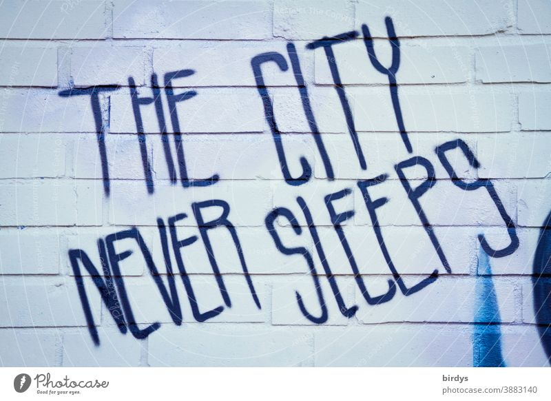 The city never sleeps. Grafitti in English script on a brick wall. Despite Corona City life liveliness Characters Graffiti lockdown Town busyness activity
