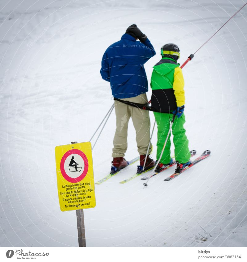 Father and child use ski lift, drag lift. Snow in the ski area. Sign that sledge drivers may not use the lift Skier Ski lift Ski tow Skiing Lift operation