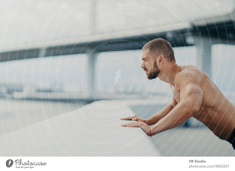 Sideways shot of handsome muscular man with thick beard does push ups exercise has workout outdoor leans on bridge fence engaged in physical activity poses with bare torso has strong muscles