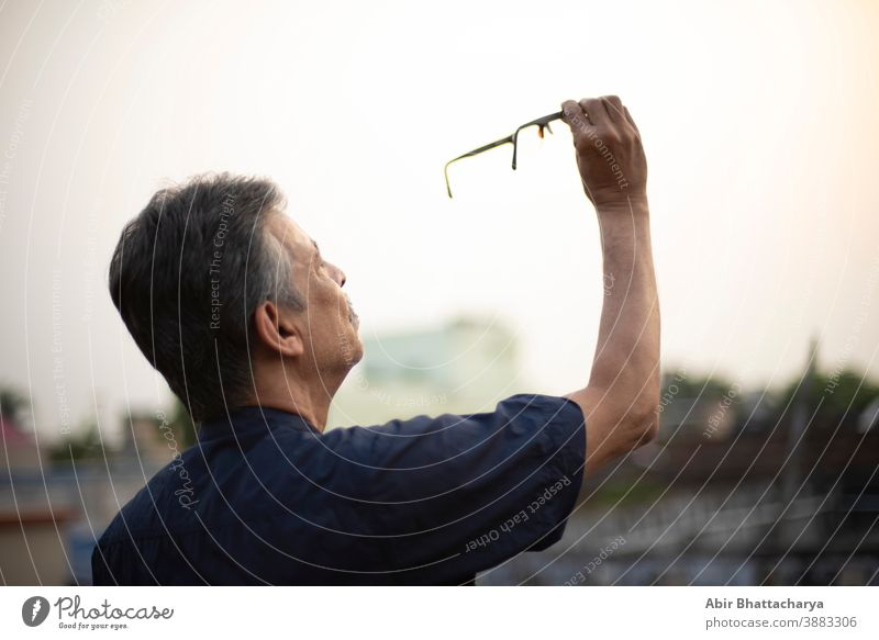 An old / aged Indian Bengali man in blue shirt is holding his spectacles up on the air to watch it carefully while standing on a rooftop under the open sky. Indian lifestyle and seniors