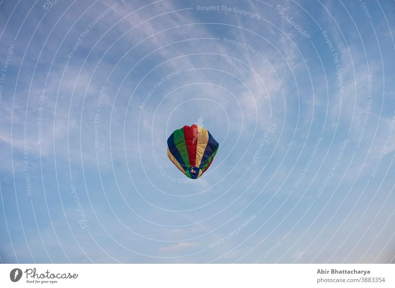 A colorful lantern/balloon is flying in the blue sky with white clouds in the afternoon of Diwali. Indian festival adventure air asia background beautiful