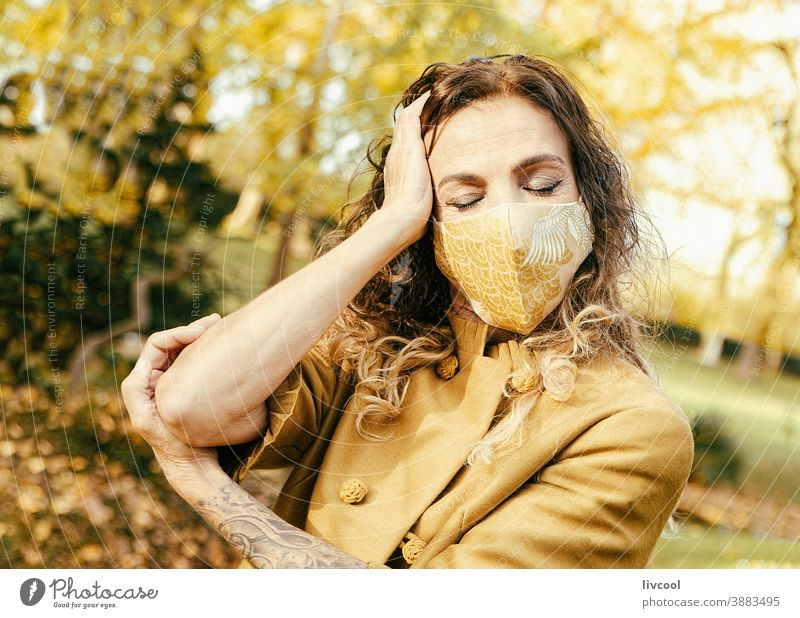 woman in yellow dress and mask in a park II retouching hair garden yellowish leafs lifestyle mature portrait one people tree coat yellow overcoat scene romantic