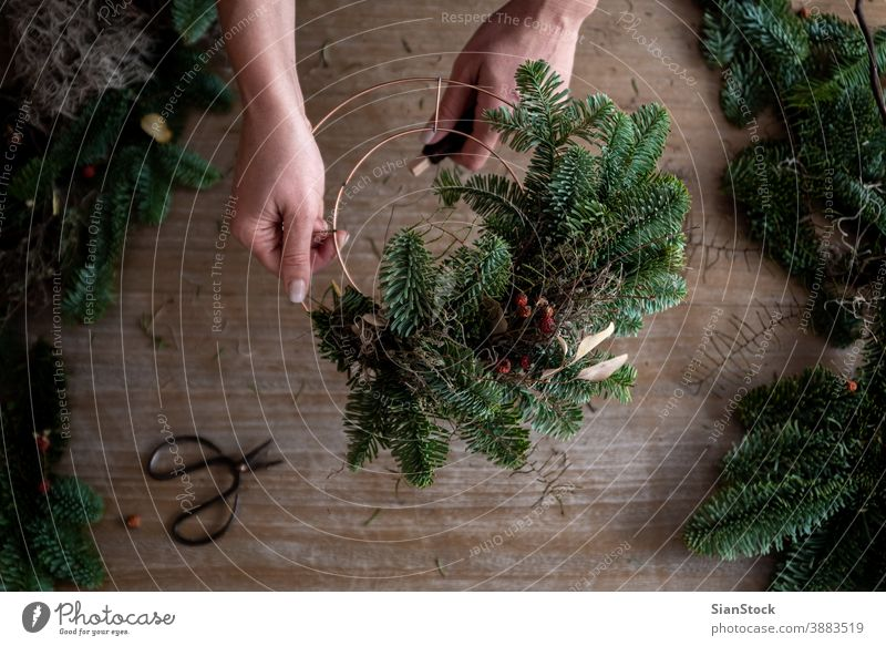 Woman making Christmas wreath of spruce, step by step. Concept of florist's work before the Christmas holidays. flat lay branches hand wooden table handicraft
