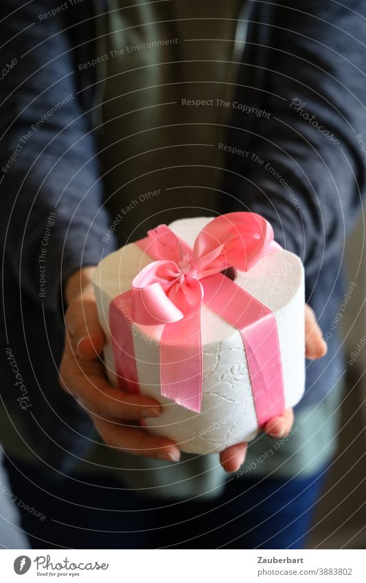 Toilet paper roll with pink ribbon is handed over toilet paper Coil Gift Pink Bow Handover corona hoard Christmas Birthday Donate Christmas gift Giving of gifts