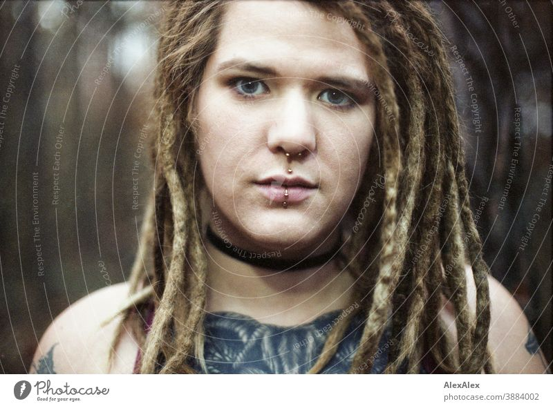 Portrait of a young woman with dreadlocks and tattoos in the forest Woman Dirty Blonde tattooing Jewellery Piercing earring Concealed Direct Nahe Skin