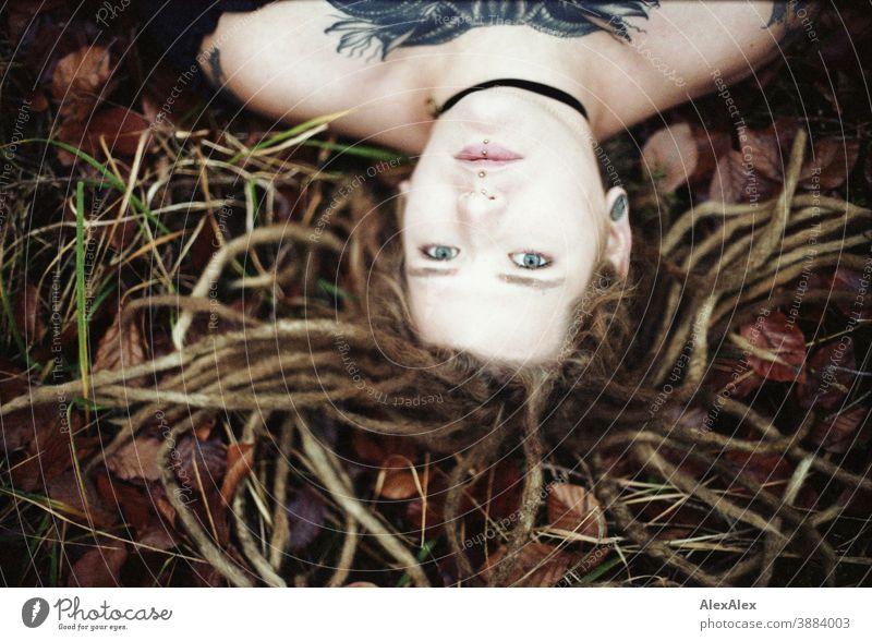 Portrait of a young woman with dreadlocks and tattoos on the forest floor in autumn Woman Dirty Blonde tattooing Jewellery Piercing earring Concealed Direct