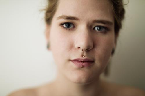 Close portrait of a young woman with dreadlocks and piercings Woman Dirty Blonde tattooing Jewellery Piercing earring Concealed Direct Nahe Skin Expression