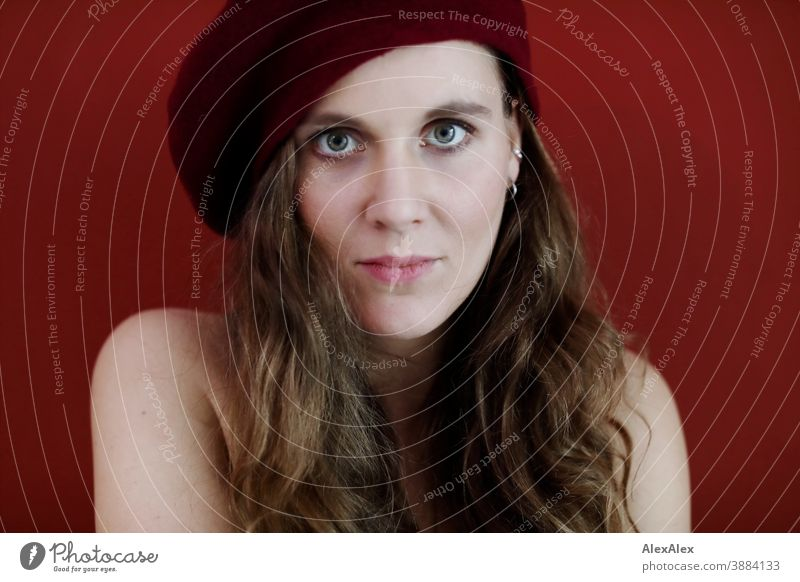 Portrait of a young woman with hat in front of a red wall Woman Slim pretty Brunette long hairs Face smart emotionally see look Looking Direct naturally