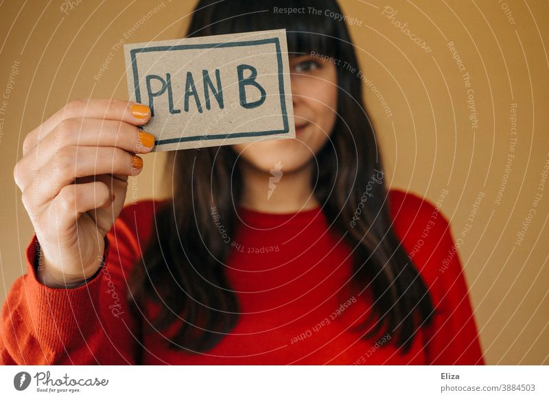 A dark-haired woman in a red sweater holds up a sign saying Plan B Woman Flexibility alternative Planning Business Human being second way of education