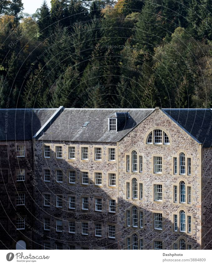 Old Disused Mill Building at New Lanark Village Scotland in Autumn Sunlight village mill disused converted building stone stonework masonry shadow shadows tree