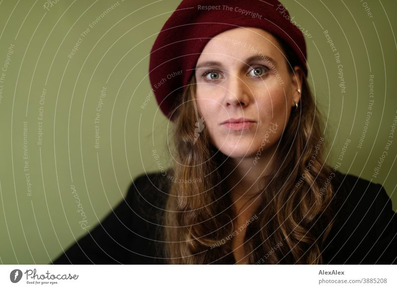 Portrait of a young woman with hat in front of a green wall Woman Slim pretty Brunette long hairs Face smart emotionally see look Looking Direct naturally