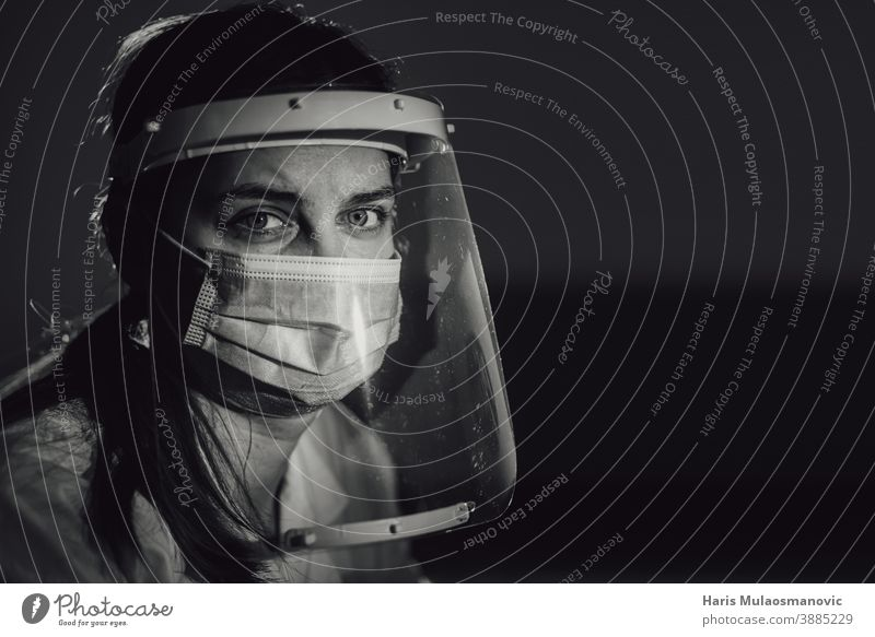 hard working female doctor, heath care worker with face shield and mask in black and white black background brazil corona epidemic corona virus covid-19