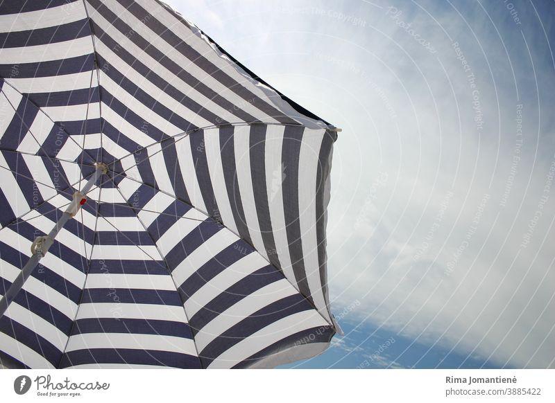 A sun umbrella against clear sky on the beach in the summertime vacation sea travel holidays blue sand relaxation beach umbrella rest recreation