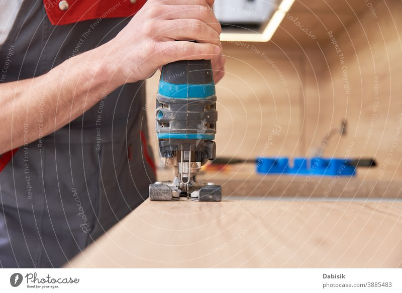 Repairman using electric jigsaw. Sawing place for installing gas hob in worktop kitchen repair countertop repairman fit construction induction improvement new
