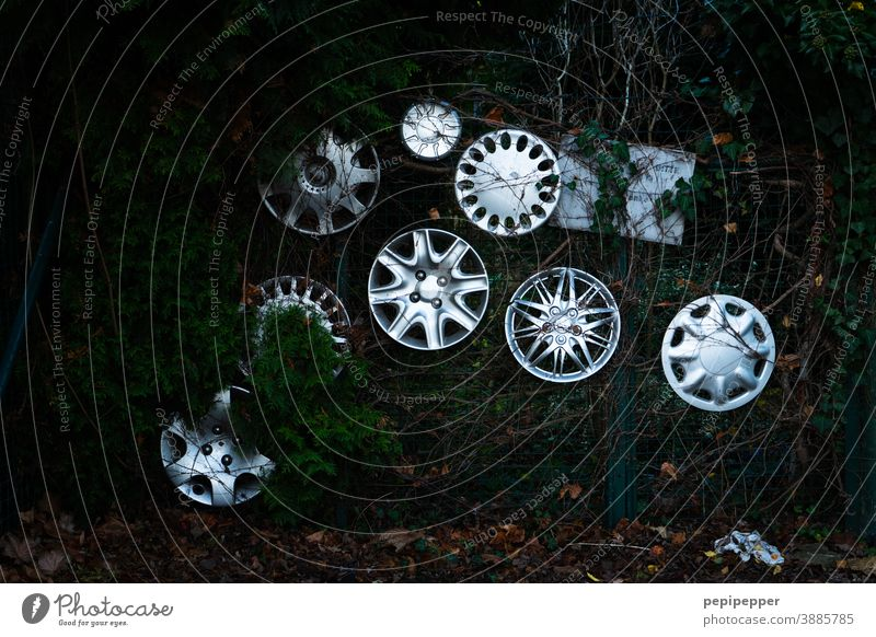Hubcap collection attached to a fence Hubcaps Car rims car accessories Motor vehicle Transport Round Fence Garden Silver Scrap metal Car body Broken Old