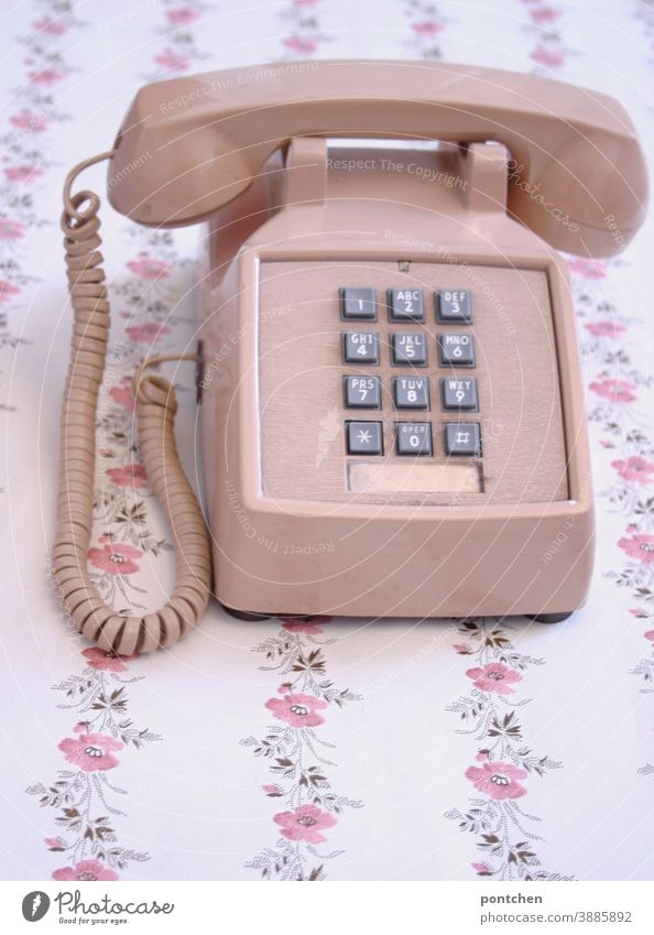 An old telephone in pink stands on a table with a flower pattern. Vintage, progress, technology, communication Telephone vintage Old Pink fumble figures