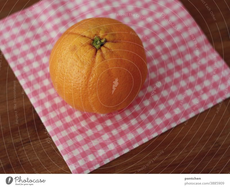 An orange one is lying on a checked napkin on a table. Vitamin C, good for the immune system Orange citrus fruit Healthy Fruit Fresh Table Food Healthy Eating