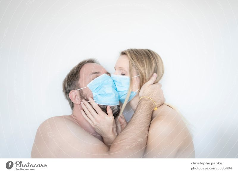 Man and woman kiss with mask Woman Mask mouth-nose protection corona covid-19 COVID coronavirus pandemic Corona virus Protection Risk of infection Virus
