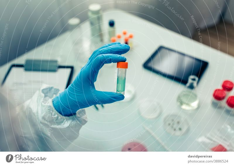 Scientist hand showing vial with vaccine scientist flask treatment coronavirus antidote cure investigation bacteriological protection suit laboratory medicine