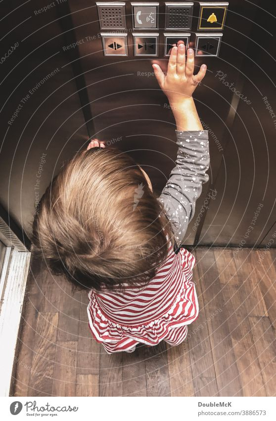 Girl pushes the elevator button and closes the door Child Toddler Colour photo Human being Day 1 - 3 years 3 - 8 years Multicoloured Pushing Elevator