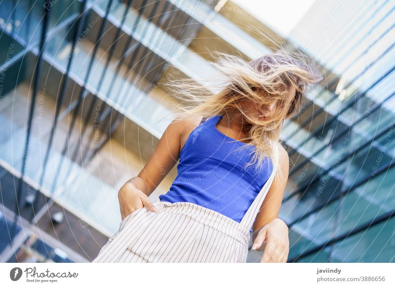 View from above of young girl moving her hair wild female person hairstyle woman beautiful city outdoors lifestyle adult urban happy street modern beauty