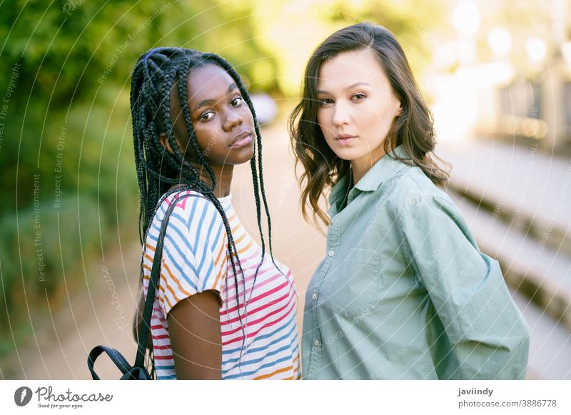 Two young friends looking at camera together on the street. Multiethnic women. multiethnic black afro girl student two fun people lifestyle smile female pretty
