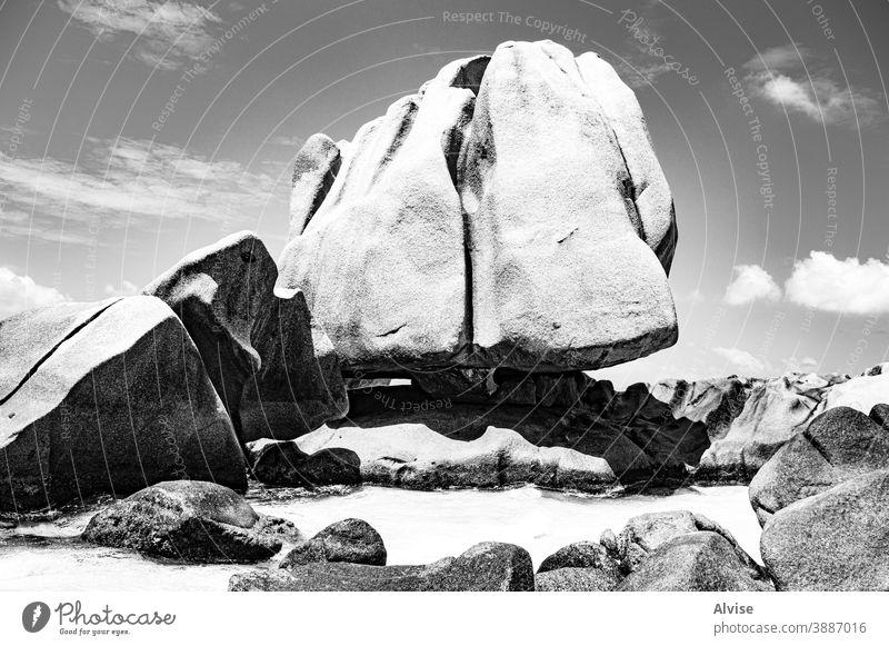 Granite monolith floats in the ocean like a giant iceberg seychelles tropical granite eroded travel nature landscape background rock erosion sand stone boulders