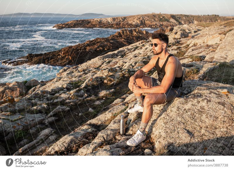 Tranquil man enjoying seascape in summer at sunset admire peaceful harmony sundown relax male rock coast calm beach shore nature sit water rest seaside freedom